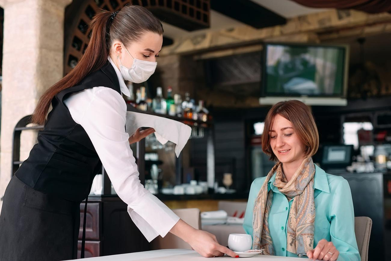 Waitress wearing mask serving coffee